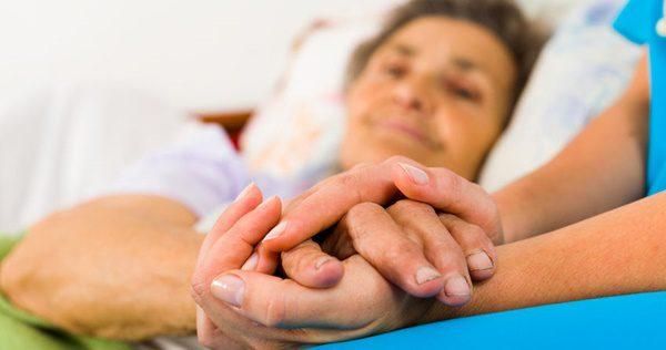 55422020 - caring nurse holding kind elderly lady's hands in bed.