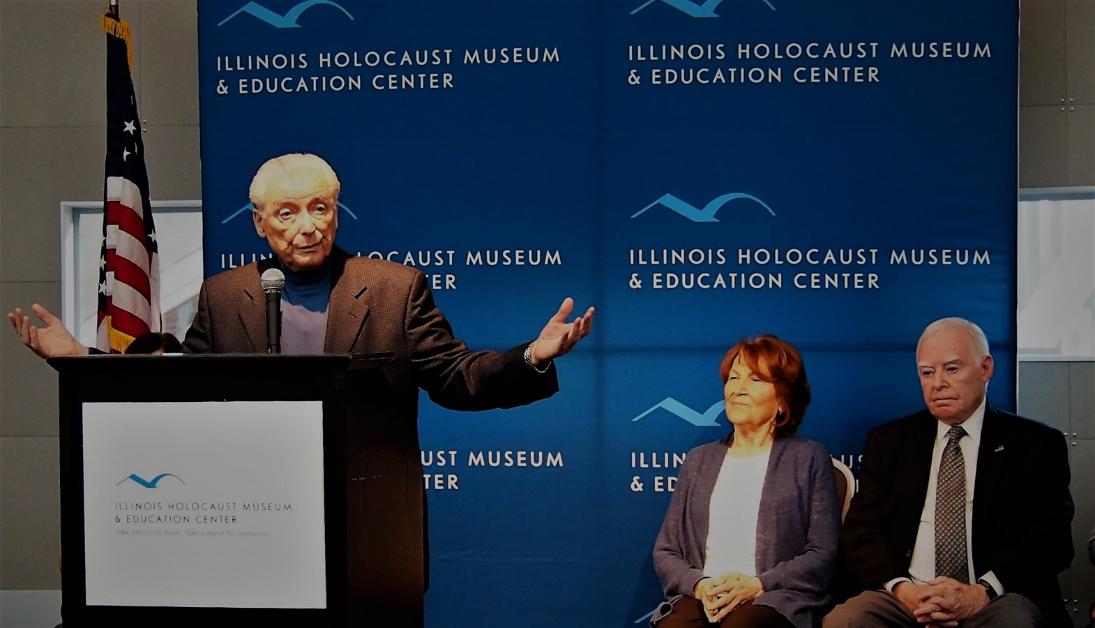 Holocaust survivors Aaron Elster, speaking, Fritzie Fritzshall and Ralph Rehbock at Illunois Holocaust Museum & Education Center. Feb 2. 2017. Source: Jonah Meadows / Patch.com / Donald Trump Refugee Ban Condemned By Chicago-Area Holocaust Survivors
