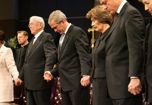 LA6G5137 President George W. Bush and Mrs. Laura Bush are seen during a prayer holding hands with former President Bill Clinton, right, and Rev.  Robert Schuller, left,  at the homegoing celebration for Coretta Scott King, Tuesday, Feb. 7, 2006 at the New Birth Missionary Church in Atlanta, Ga.  White House Photo by Eric Draper