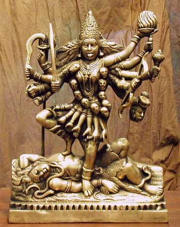 "Statues of Kali, often seen at burial sites, portray a black woman with four arms. In each hand she holds a scimitar, a demon's head, a ""blessings,"" and either a spear or trident. She always wears a necklace of skulls and earrings of demon heads. Blood also streams from her tongue onto her body. Around her waist is a skirt made of hands."