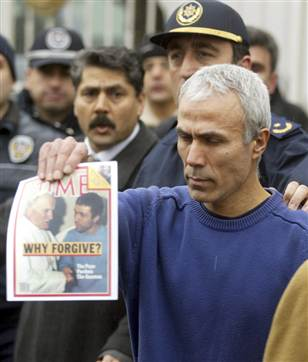 Mehmet Ali Agca, the gunman who shot Pope John Paul II in 1981, holds up an issue of Time magazine outside a military recruitment center after being released from prison in Istanbul on Thursday. Agca served more than 25 years behind bars in Italy and Turkey.