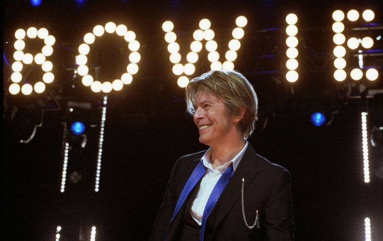 What did the spotlight miss about Bowie? (David Bowie performs at Tweeter Center, August 8, 2002, Photo by Adam Bielawsk; Source: Wikimedia Commons, CC-by-SA 3.0)