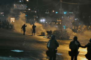 Police officers using tear gas during the first wave of the Ferguson unrest.  Source: Wikimedia Commons.
