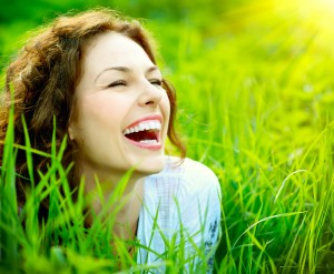 Image description: a white woman lies in the grass, laughing.