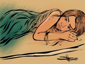 Image: young woman lying on her side, looking sad