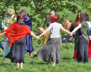 Image description: Pagans in festive dress hold hands in a circle in a grassy field.