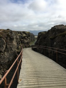 Image: two cliffs with a wooden walkway between them.