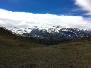 Image: a grassy hill with a snowy glacier and clouds beyond it.