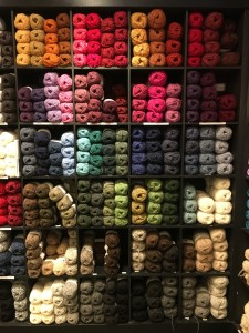 Image: multicolored skeins of yarn on a set of floor-to-ceiling shelves.