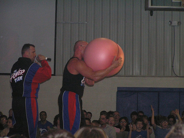 Power Team member blowing up a hot water bottle. Photo by Stevan Sheets, Flickr.