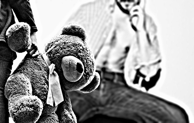 A teddy bear in a child's arm, while an adult looms threateningly in the background