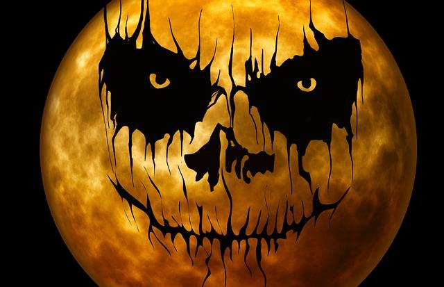 A creepy pumpkin face superimposed on an orange moon