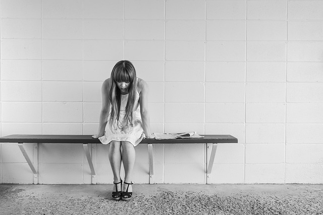 A girl sits alone on a bench, her head towards the floor.