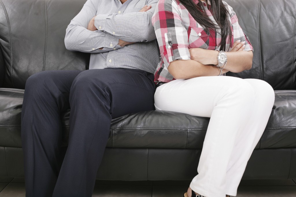 Couple sitting of the couch having problems in their relationshi