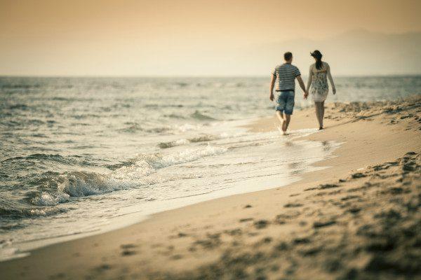 couple holding hands beach