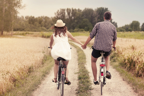 couple on bikes holding hands