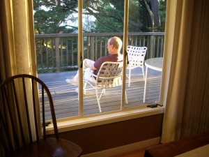 Jon Newhall reading on the deck of his house, suggesting a mood of mediation.  Photo by Barbara Newhall