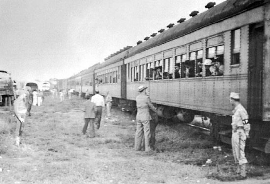 Military police stand guard as trains arrive at the camps. American military police. In California. (Photo by Robert Ross)