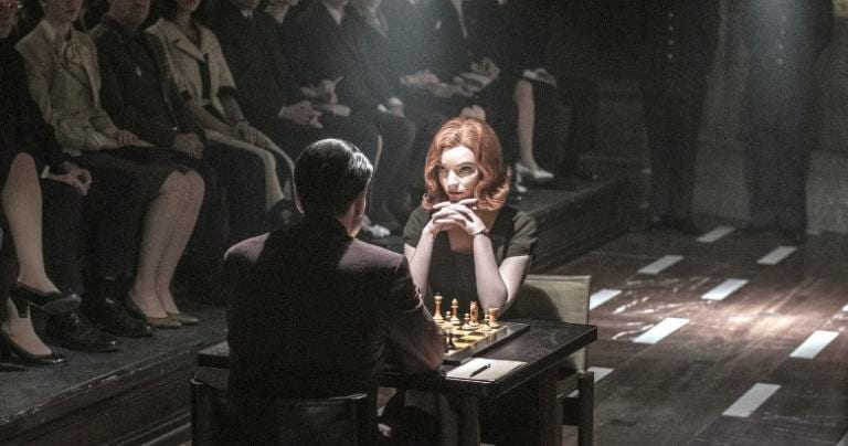 A man and a woman playing chess in a tournament, with an audience present