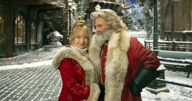 Santa and Mrs. Clause in a snow-covered North Pole village.