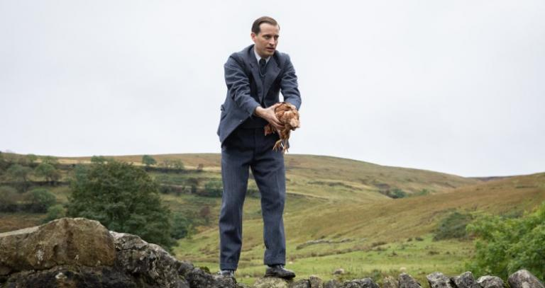 A man holds a chicken with the English countryside in the background