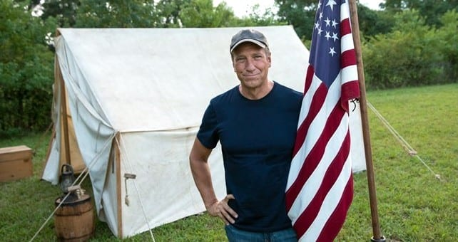 Mike Rowe stands next to an American flag in front of a tent