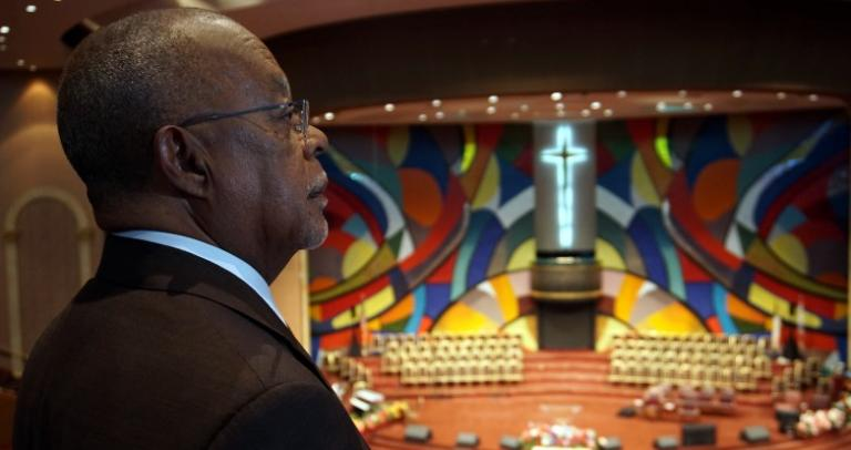 Dr. Henry Louis Gates gazes at a mural at the front of a large church building.