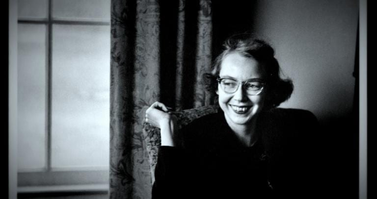 Writer Flannery O'Connor sits next to a window, smiling