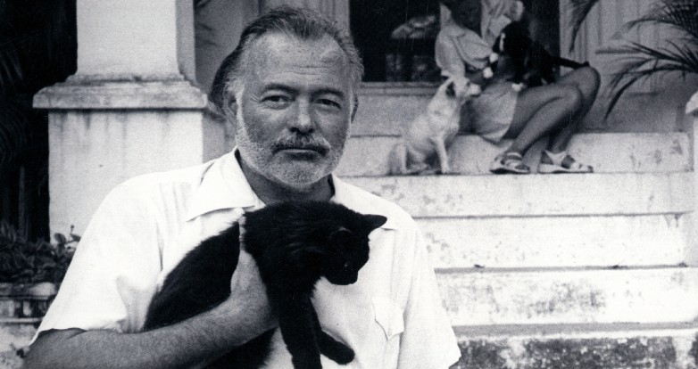 Writer Ernest Hemingway sits in front of his home in Cuba, holding a cat, while wife Mary sits behind him on the steps, with more cats and a dog.