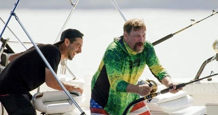 Fishermen laugh while aboard a boat.