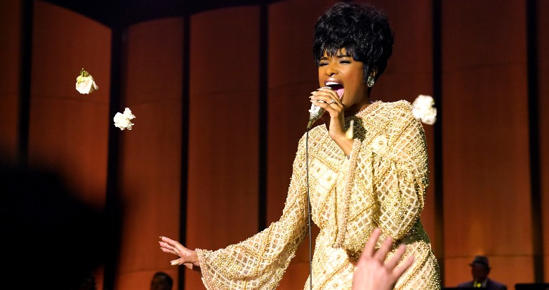 Jennifer Hudson performing in a 1960s gown as Aretha Franklin, as audience members throw flowers.