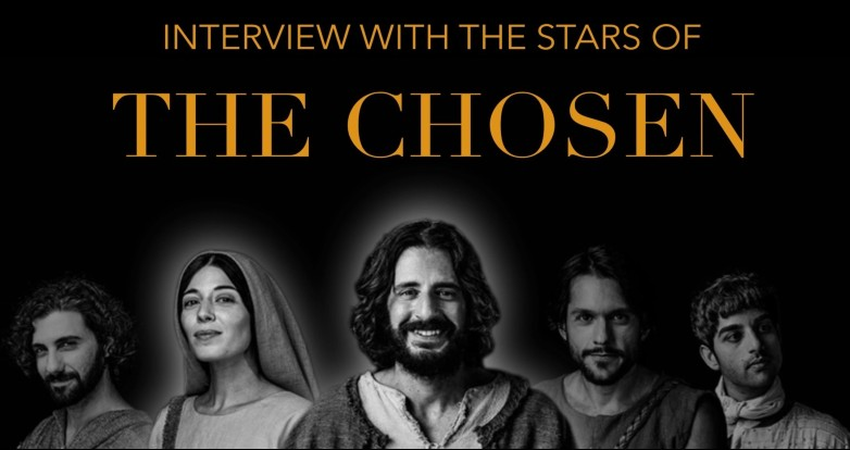The cast of the Biblical series 'The Chosen.' with Jonathan Roumie at center, poses against a black background.