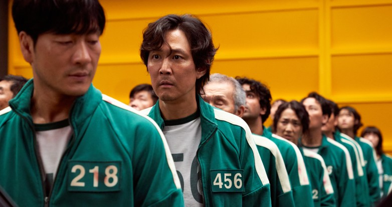 Two men in numbered tracksuits stand in a line with other people dressed the same.