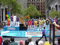 """gay Christians on a cheery float, wearing brightly colored t-shirts that spell out """"HOPE"""""""
