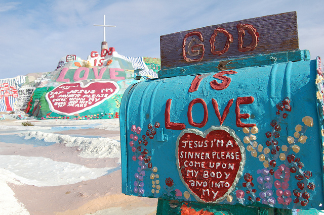 """Photo of Salvation Mountain, a brightly painted mountain with Bible verses and a sign that says """"God is Love"""""""