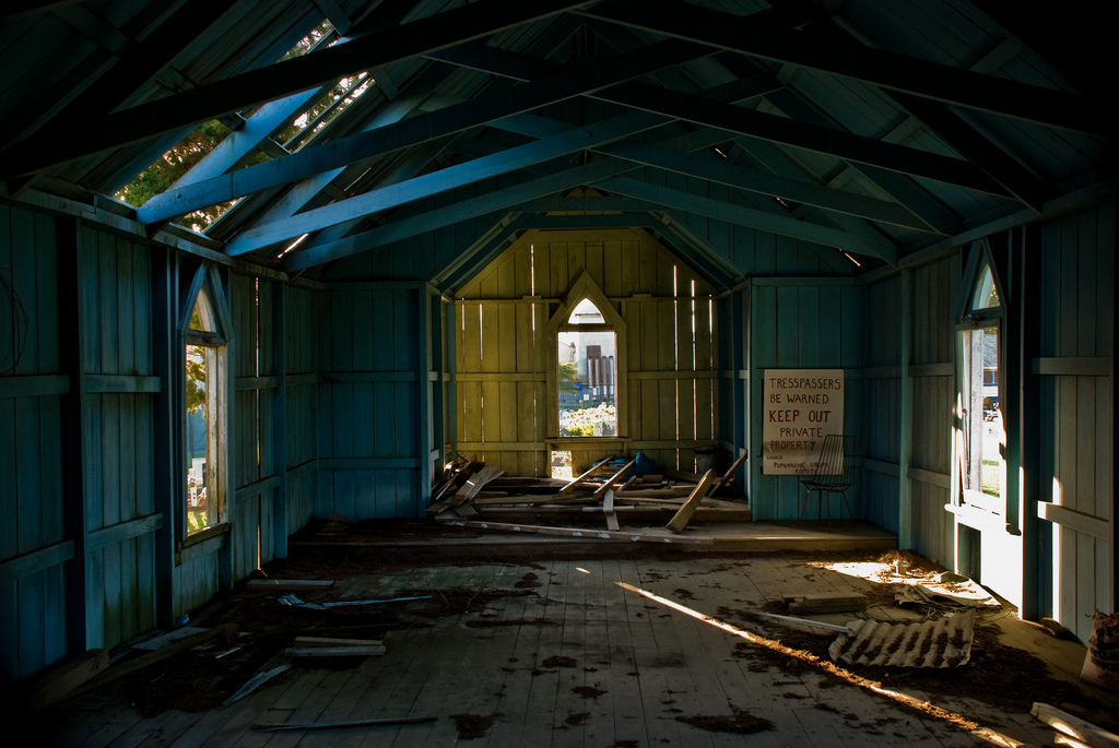 An abandoned church in New Zealand--and a sign of the times. (Phillip Capper, CC.)