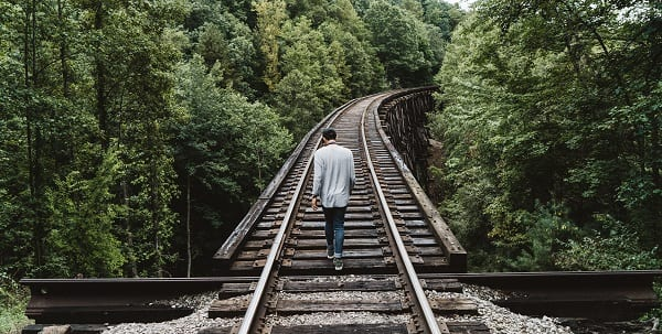 man walking along train tracks in the forest