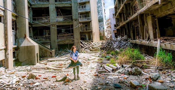 woman in schoolgirl costume roams the ruins of gunkanjima in japan