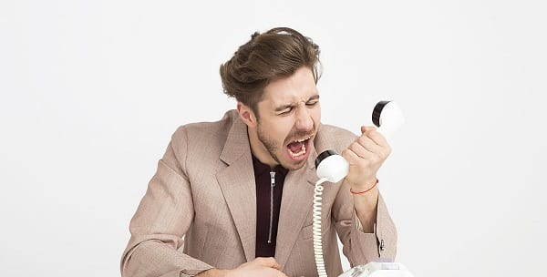 angry businessman screaming into a landline phone