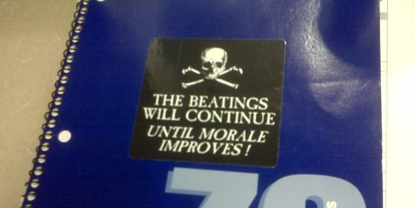 "a manager's notebook with a sticker: ""The beatings will continue until morale improves"""