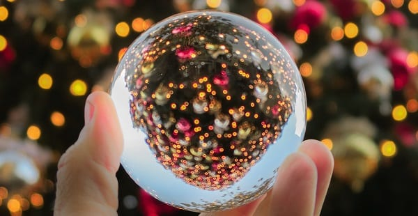a multifaceted bauble in front of a lit christmas tree