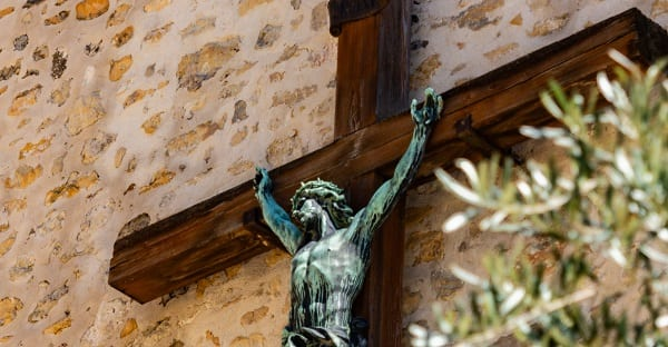 a crucifix affixed to the outside of a church wall in france