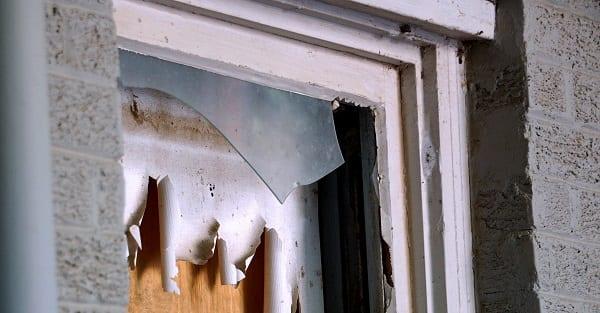 a broken boarded up window