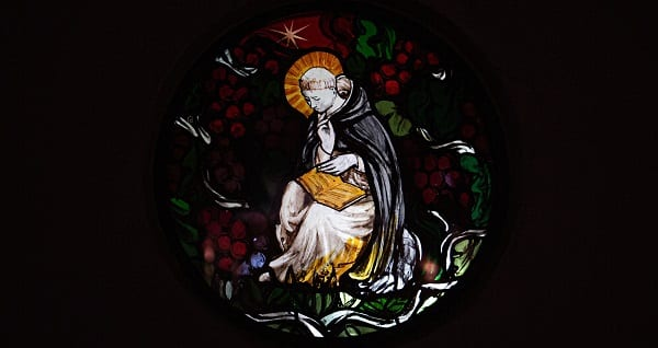 a monk on a stained glass window faces a reckoning
