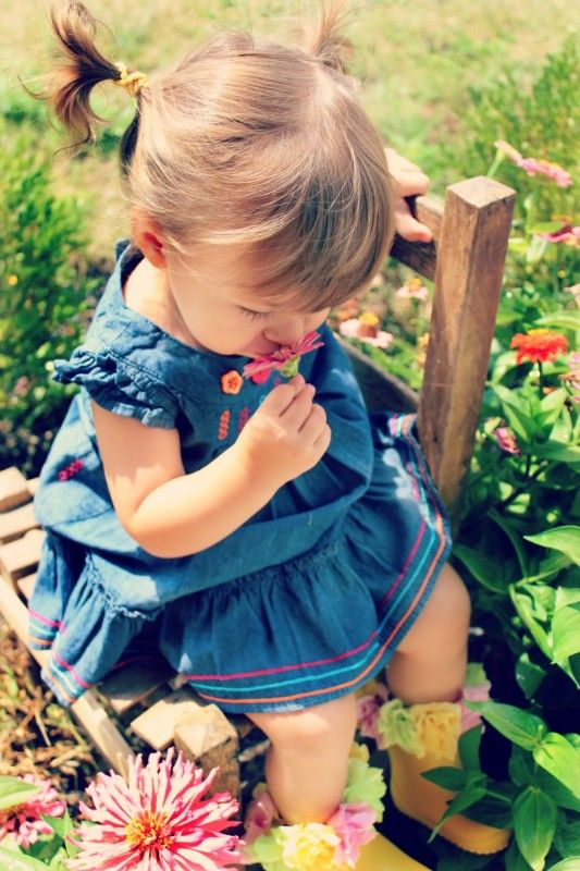 child smelling flowers