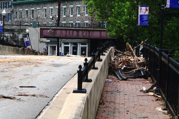 Bridge into Ellicott City, MD, showing flood damage and debris; iconic railroad bridge in background.