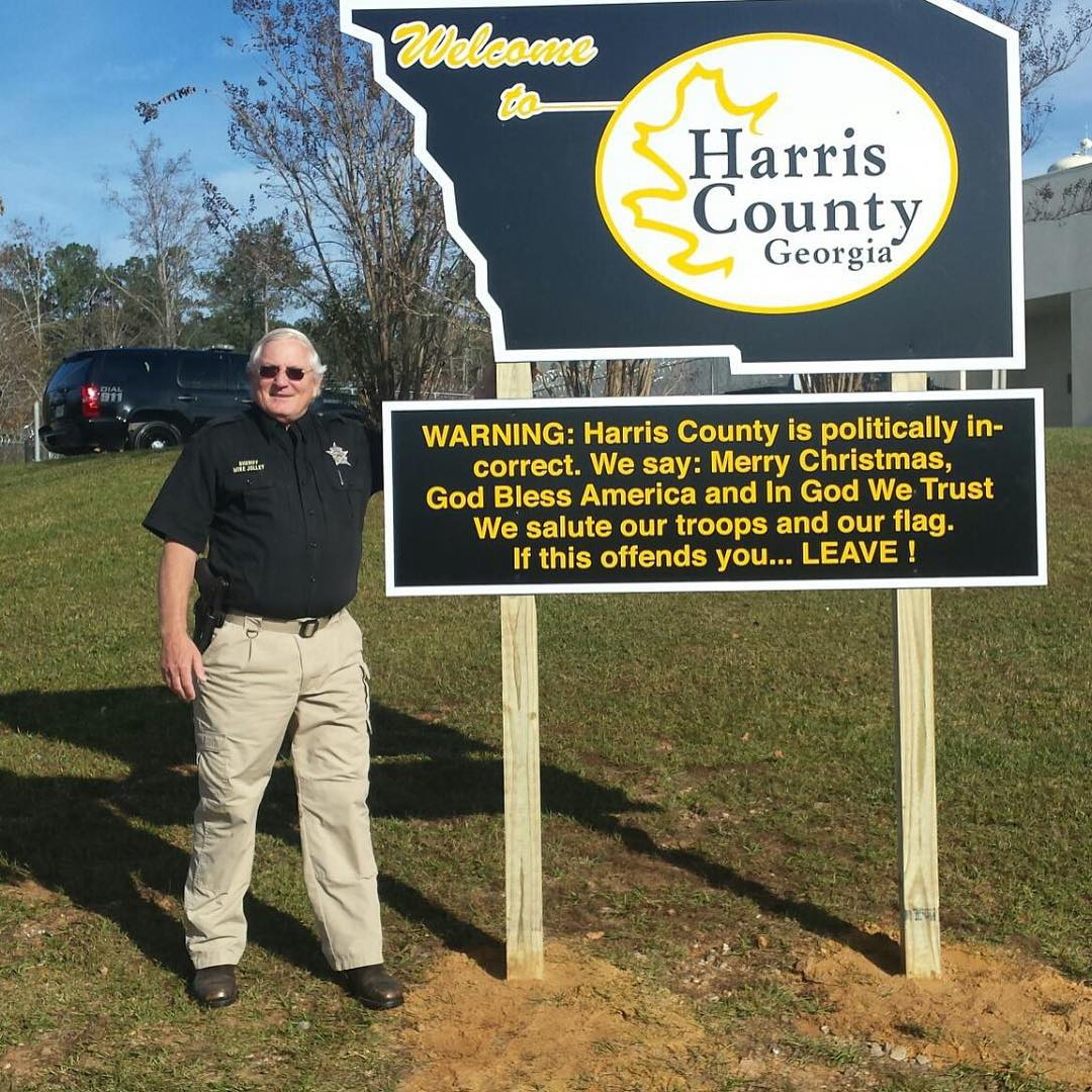 An insecure Sheriff Jolley standing next to his belligerent sign. Via Jolley's instagram.