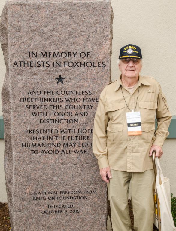 FFRF board member, lifetime member,  and veteran, Joe Cunningham stands beside FFRF's Atheists in Foxholes monument. Photo by Andrew Seidel