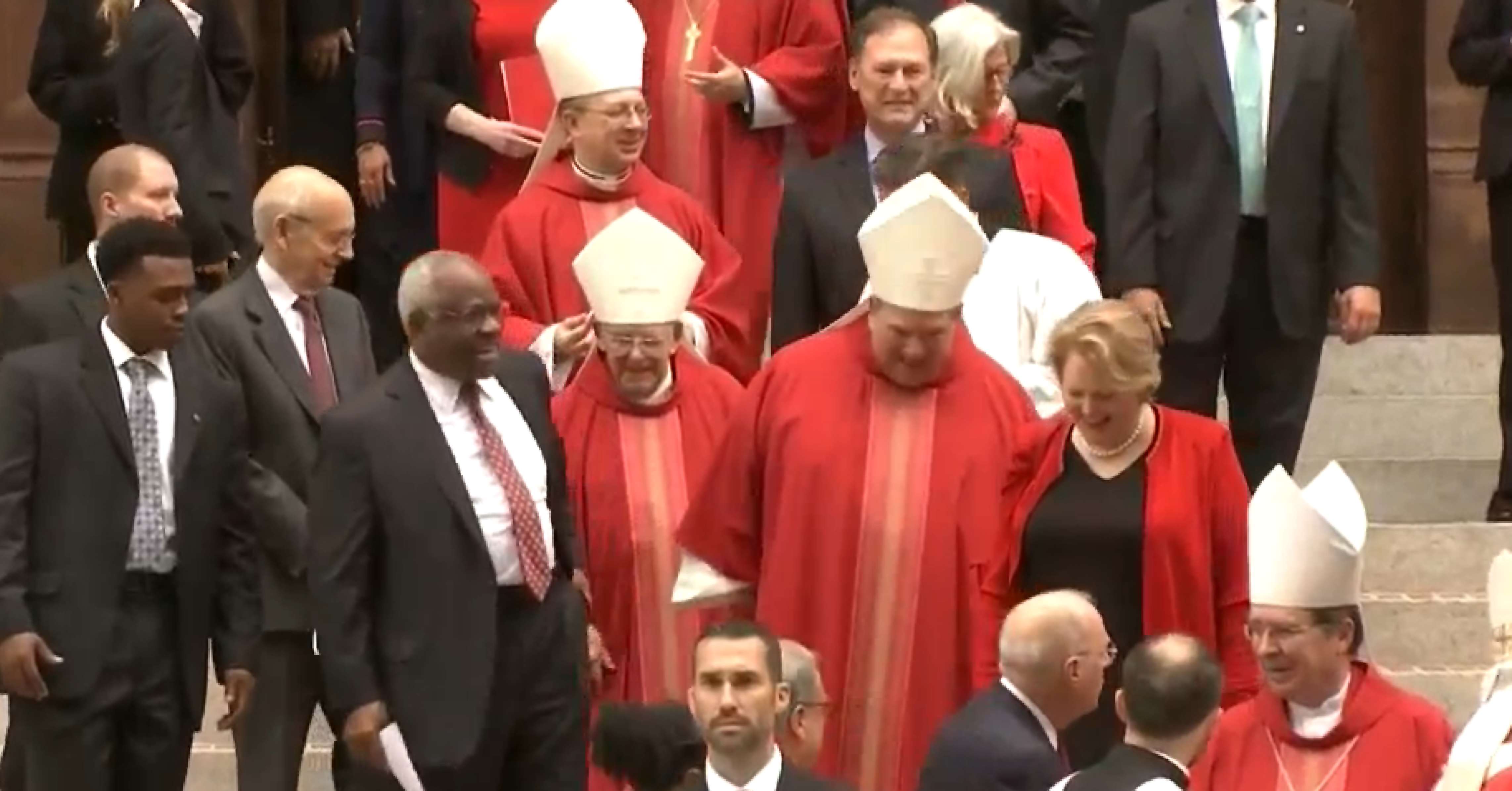 Screenshot of Justices Thomas, Kennedy, and Alito among the red clad clergy, exiting the mass. Courtesy of C-SPAN