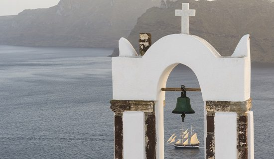 Inside the majesty. Traditional church belfry and sailing boat at sunset in Oia, Santorini, Greece